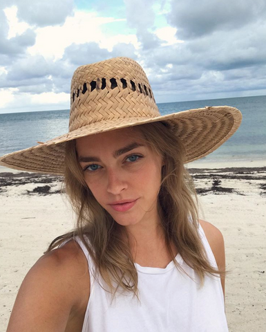 Paula Magyar walks on the beach wearing a straw wide-brim hat and a white tank top.