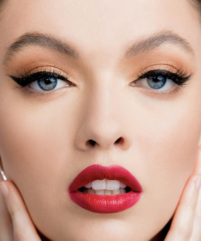 A close up picture of a model with cat-eye makeup and bold lips done by Kristofer Buckle.