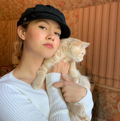 Iris Apatow takes a picture with her cat wearing a black hat and a white shirt