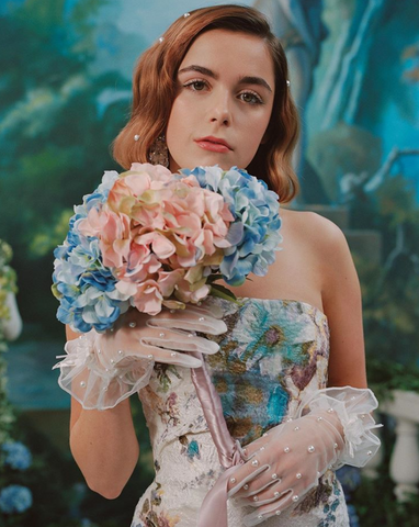 Kiernan Shipka is photographed in a floral gown while she holds a bouquet of blue and pink hydrangeas.