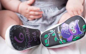 "Baby shown wearing chalkboard shoes decorated with owl on the right and the words ""6 months old"" on the left in pink"