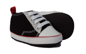Baby shoes shown in black sneaker style with red piping. Right shoe is facing to the right. Left shoe is on it's side displaying the chalkboard sole.
