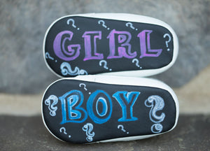 This photo shows the chalboard sole of two shoes. The top shoe says GIRL in pink, surrounded by question marks. The bottom shoe says BOY in blue, surrounded by question marks.