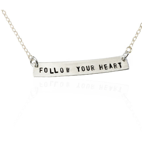 rectangle pendant hand-stamped with the words FOLLOW YOUR HEART