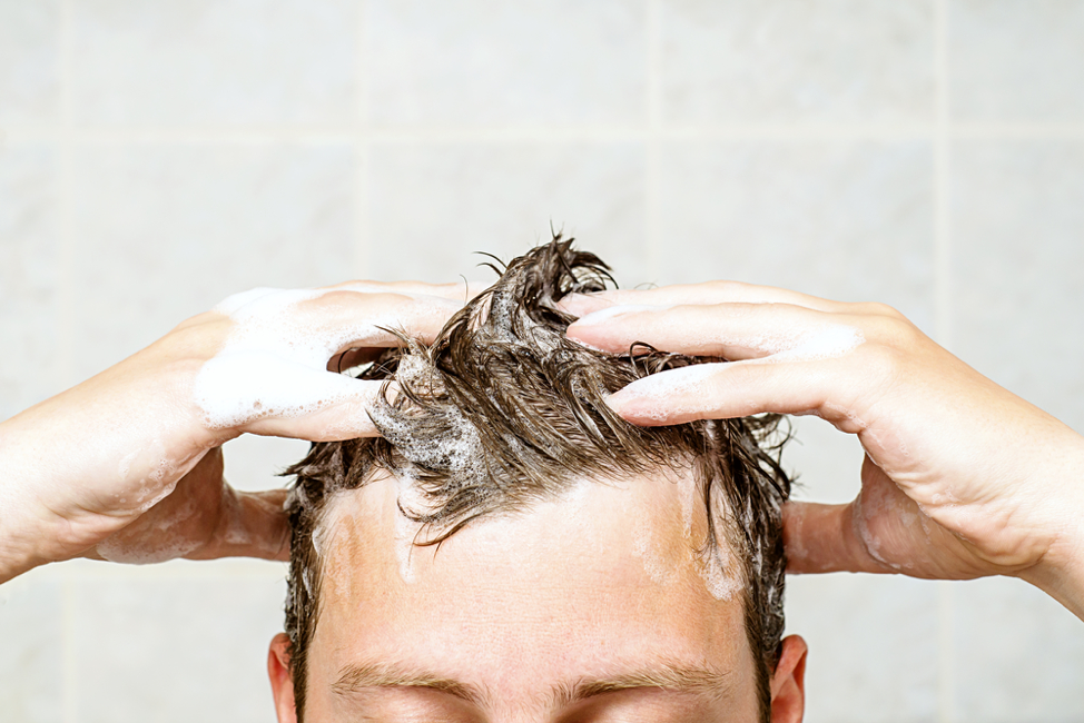 man washing his hair with shampoo