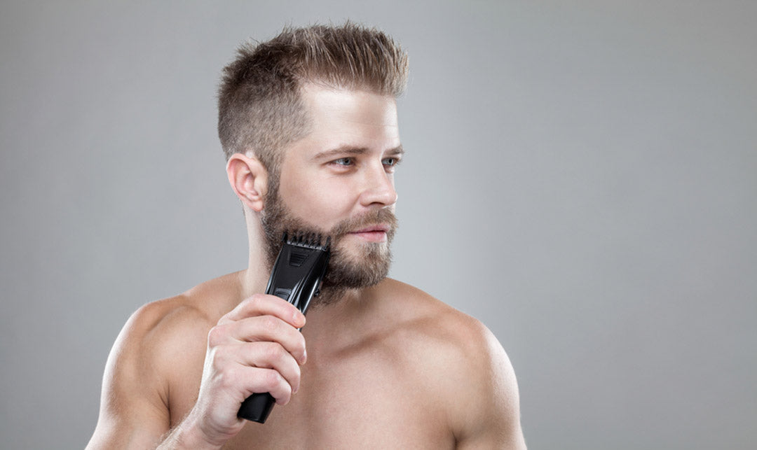 bearded man trimming his beard