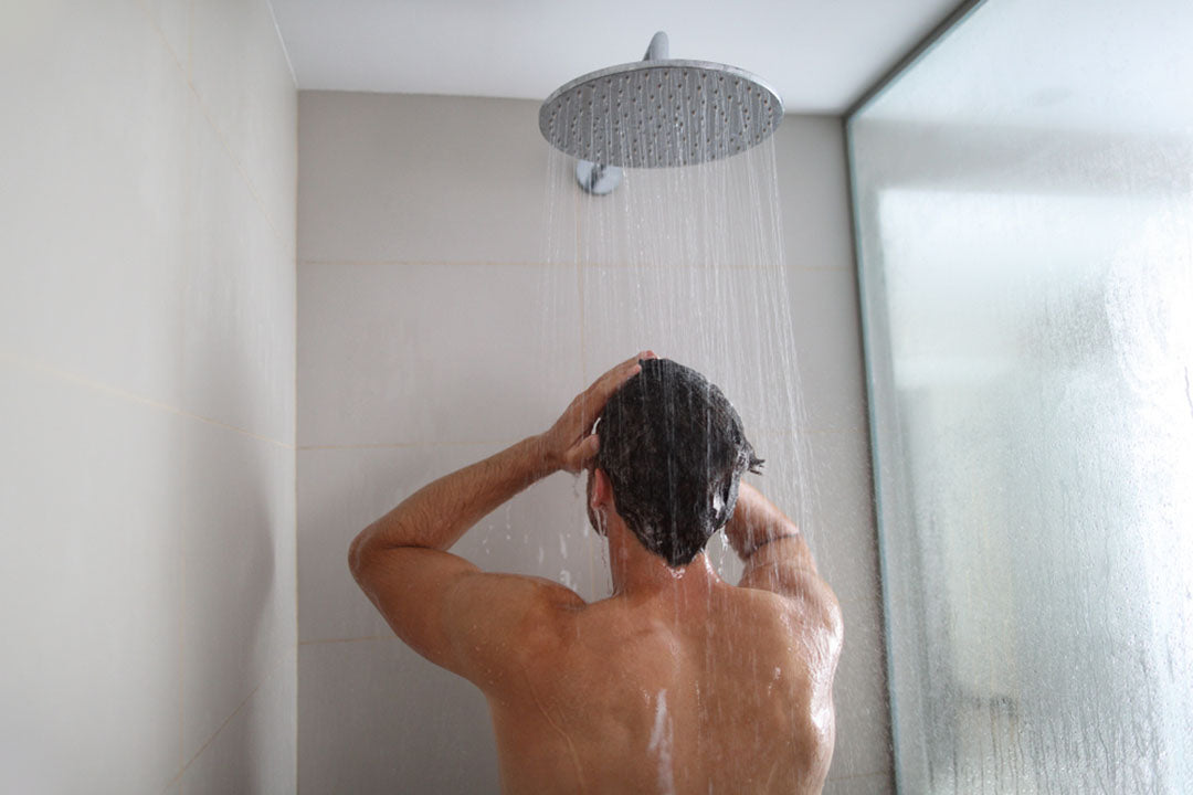 man standing under shower head
