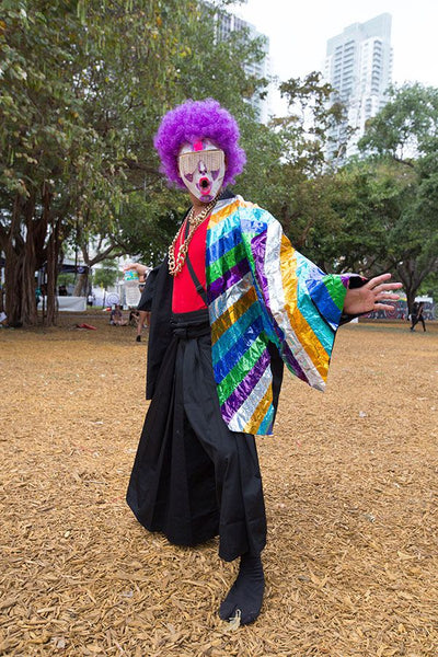 A man with a face painted like a clown wearing a bright purple wig and a japanese inspired festival outfit stands in a field posing.
