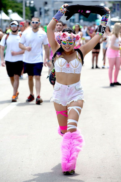 Girl wears a bright white and pink festival outfit and smiles in the sun