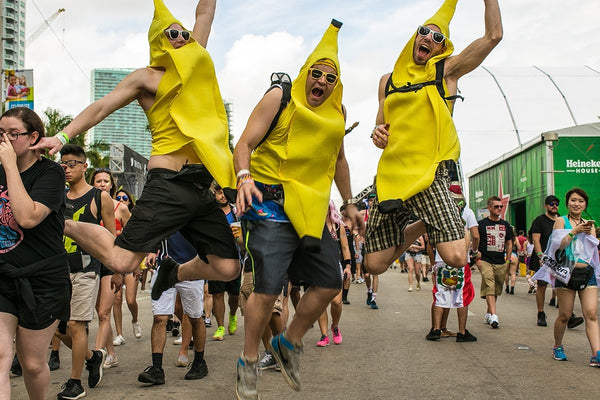 Three men in banana outfits jump in the air