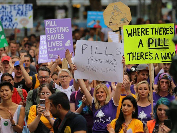 Protesters hold signs petitioning for the introduction of pill-testing