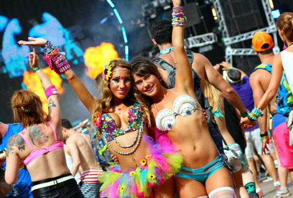 Two girls in bright tutus and bralettes throw their hands in the air in the middle of Ultra Festival