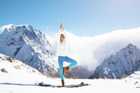 woman does yoga in snow