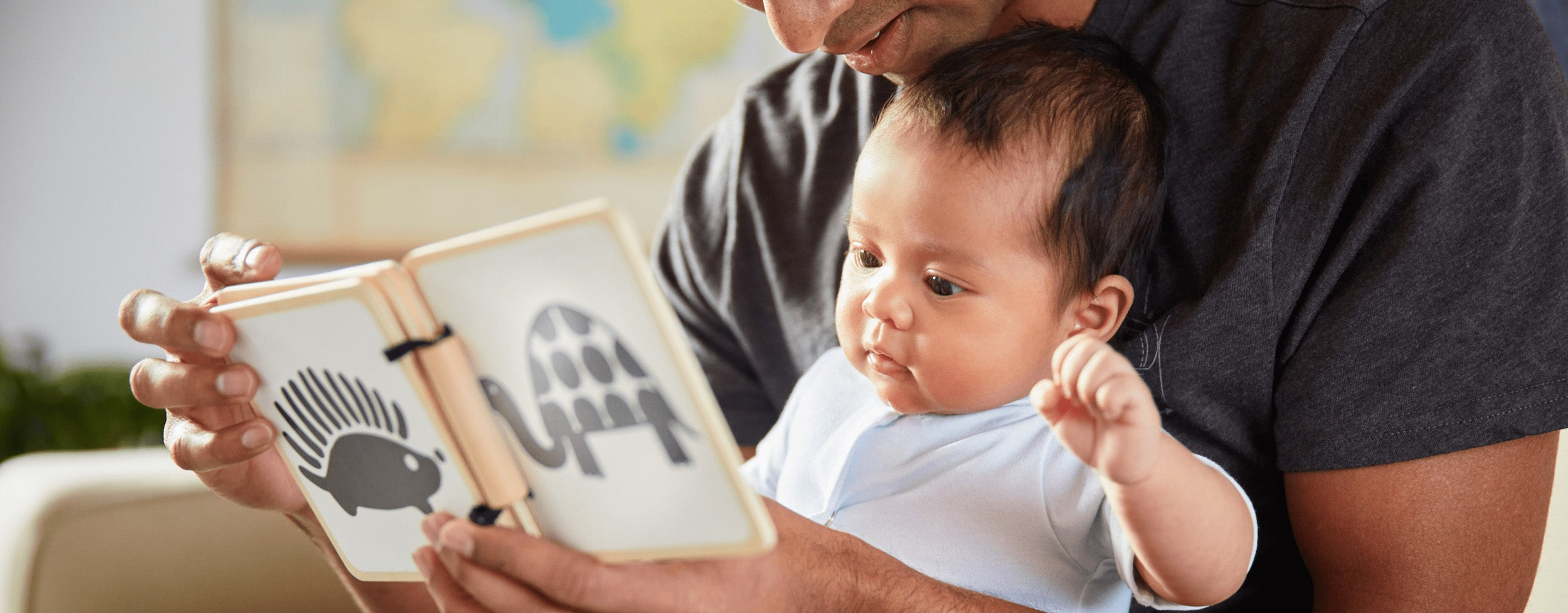 parent showing baby a book with black and white patterns