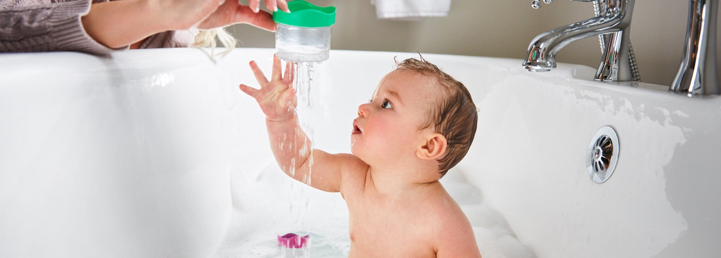 baby in bathtub looking at water poured out of plastic continer