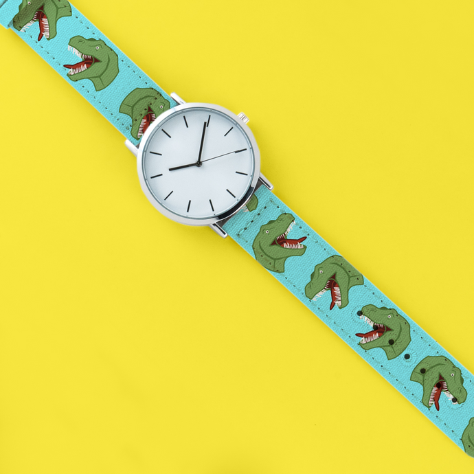 A 40mm unisex stainless steel quartz powered watch with a Screaming T-Rex pattern printed on the strap