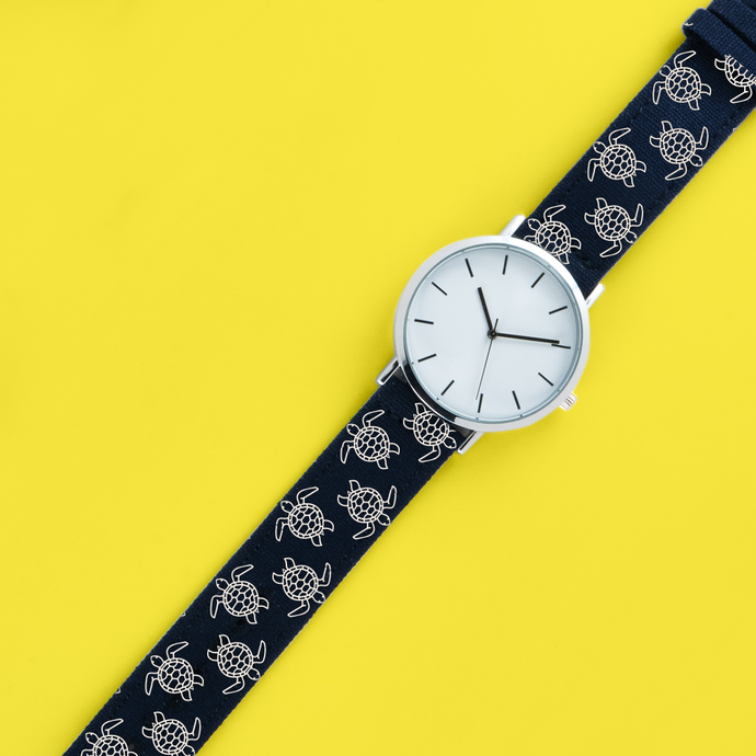 A 40mm unisex stainless steel quartz powered watch with a Surfing Turtles pattern printed on the strap