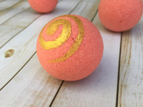 brick red bath fizzy with golden spiral painted on
