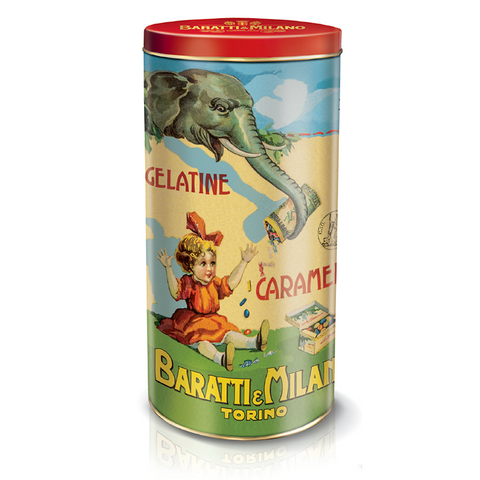 This playful Baratti and Milano tin of Fruit Gelees is tall and cylinder shaped with images of a young girl sitting down and receiving candy from an elephant! All on a white background.