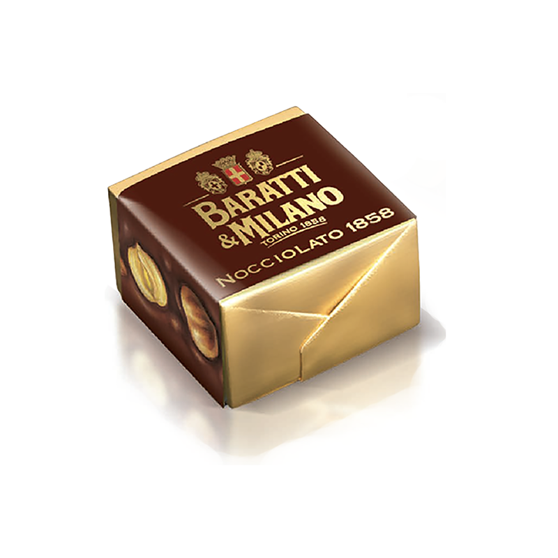 This Baratti and milano cremino is a square cube wrapped in gold foil and wrapped in a brown paper that depicts the whole hazelnuts on the sides, on a white background.