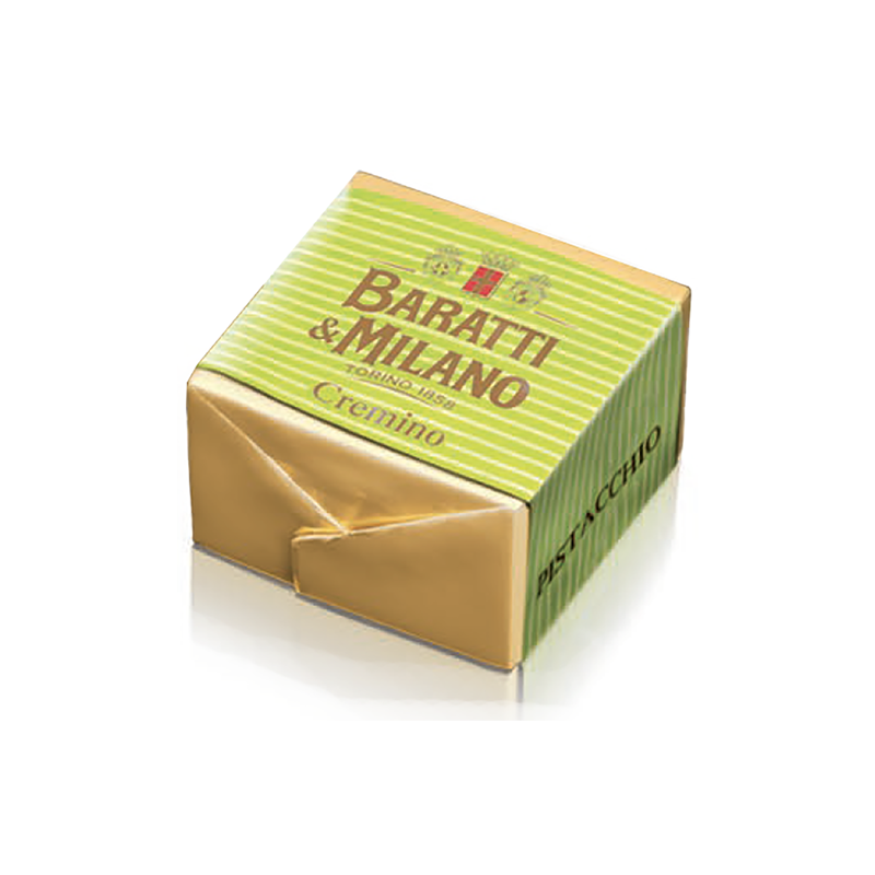 This Baratti and Milano Pistachio Cremino is a square cube of cut chocolate, wrapped in gold  and re wrapped in a bright green stripped wrapper, on a white background.