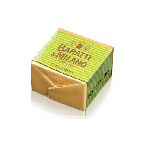 This Baratti and Milano  pistacchio cremino is squadre cube of cut chocolate, wrapped in gold gold and wrapped in a bright green stripped wrapper, on a white background.