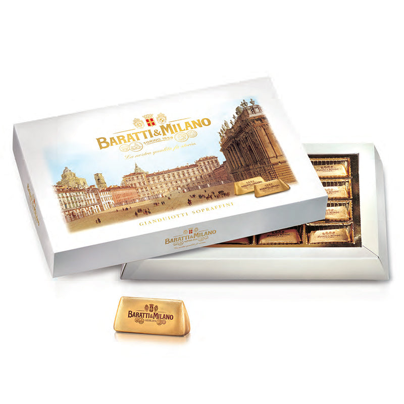 The Baratti & Milano Italian Chocolate Queen's Square Gift Box of Gianduiotti features vintage artwork and contains Baratti and Milano's world famous and royal chocolate invention, Gianduiotti. A delectable mix of Baratti's famous milk chocolate and Europe's best milk from Normandy France. The gift box displays a gold foil sketch of the Piazza Castello in Turin, the Queen's Square and her palace. The box is left slightly ajar to enjoy the visually stunning gold foil wrapped Gianduiotti chocolates.