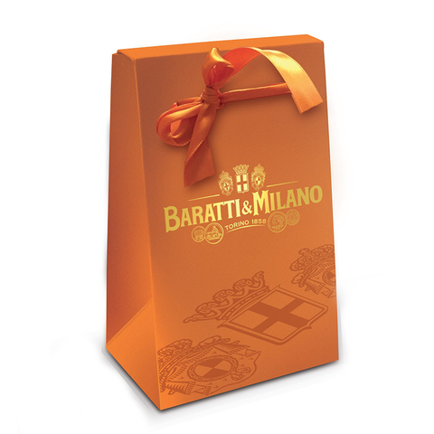 Baratti & Milano Orange Amenity Favor Ballotin of Gelées is a special way to wow your guests with a luxuriously packaged Ballotin filled with fruit forward Gelées. Image shows an elegant Ballotin in regal orange with a hand tied orange ribbon and Baratti & Milano logo in gold with whimsical portrayals of regal crests all on a white background.