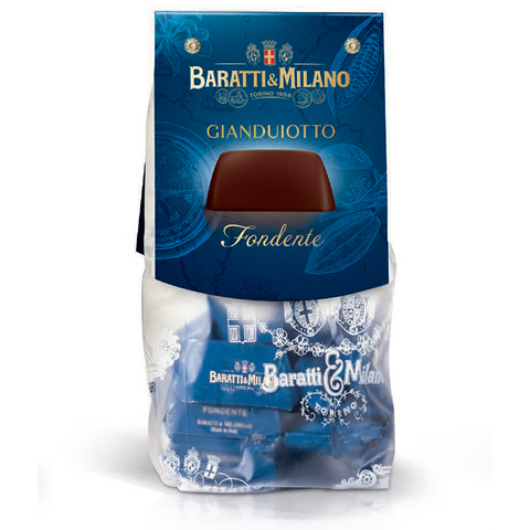 Baratti And Milano Gianduiotto Fondente Dark Chocolate Gianduja  comes in a playful peek a boo baggie allowing you to visually see the chocolates inside wrapped individually in Royal Blue. Image is on a white background.