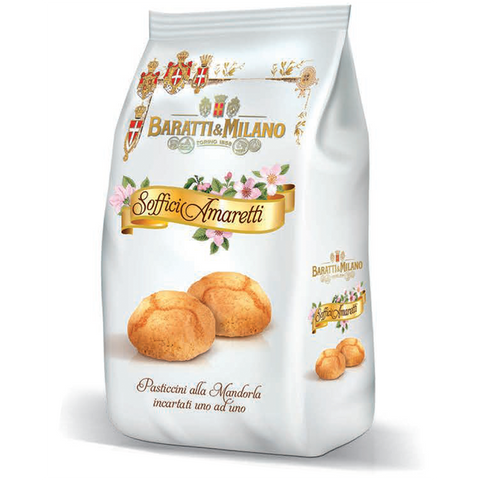"Baratti & Milano soft Amaretti cookies are packaged in an elegant white with whimsical imagery of flowers and Royal crests and ""Soffici Amaretti"" written on a gold ribbon strand on the package on top of the image of two Amaretti cookies. All on a white background."