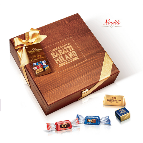 Baratti and Milano Wooden Box of Assorted Pralines is a stunning and elegant way to present an assortment of Baratti and Milano Chocolates. Image is of an elegant brown box with stunning gold ribbon around it with Baratti and Milano logo in gold. Also in the image are the four chocolates that are contained in this assortment each individually and stylishly wrapped. All on a white background.