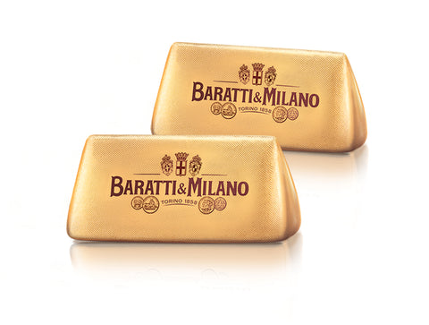 Two Baratti and Milano Gianduiotti wrapped in a magnificent gold labeled with Baratti and Milano logo in luscious brown on a white background.