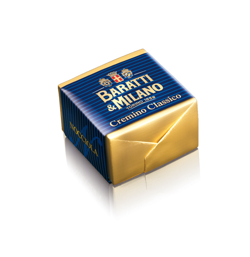 The Baratti and Milano Cremino Classico is wrapped in a Regal gold topped with the signature blue lightly stripped paper and with Baratti & Milano logo in classic gold. The square Cremino is on  a white background.