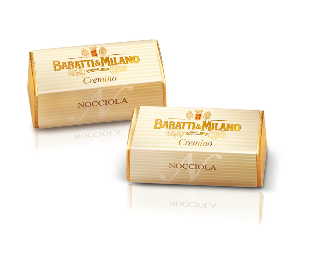 The two Baratti & Milano Hazelnut Cremini are packaged in a rectangular wrapped of gold with another elegant cream colored paper on top labeled in the gold Baratti and Milano logo with cream and white stripes on a white background.