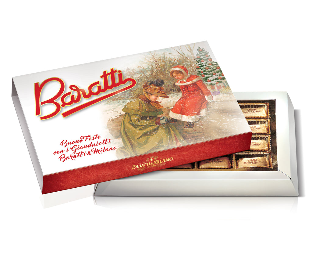 Baratti & Milano Holiday Box of Gianduiotti is a beautiful box of elegantly Gold foil wrapped chocolates in a festive timeless Baratti box cover with whimsical images of a woman helping a festively dressed little girl with her shoe and they are in fron of a Christmas tree with a light snowfall and Baratti logo in red. All on a white background.