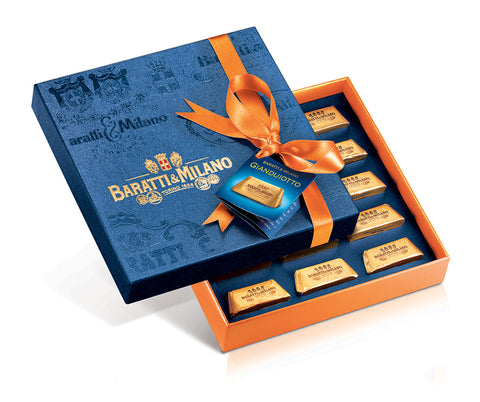 Spectacularly stunning Baratti & Milano Prestige Gift Box of Gianduiotti is a striking Royal blue box wrapped in a luxury orange ribbon containing elegantly gold wrapped gianduiotti chocolates. All on a white background.