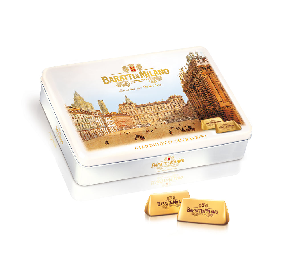 Baratti & Milano Piazza Castello Tin of Gianduiotti contains 450 grams of Baratti and Milano's world famous and royal chocolate invention, Gianduiotti. Packaged in a an elegant white keepsake tin with a depiction of the Piazza Castello in gold. Also shown on the package are the elegantly wrapped Gianduiotti chocolates in regal gold.