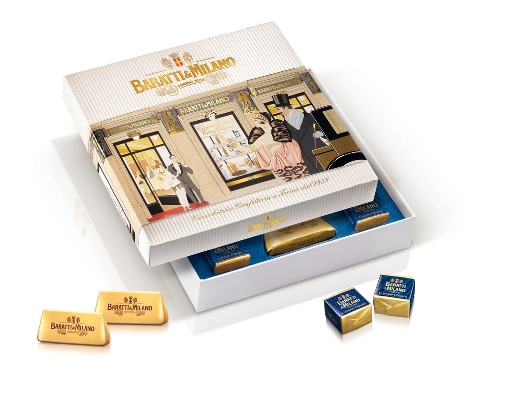 Baratti & Milano Historical Café Gift Box contains Baratti & Milano's two most famous chocolates, the gold wrapped gianduiotti & royal blue wrapped cremini, together in one beautiful box, depicting a scene from the Historic Café in Turin. Packaged in an elegant cream box with regal gold Baratti & Milano logo and depiction of people leaving and awing at the wonder that is the Baratti & Milano Historic Café in Turin.