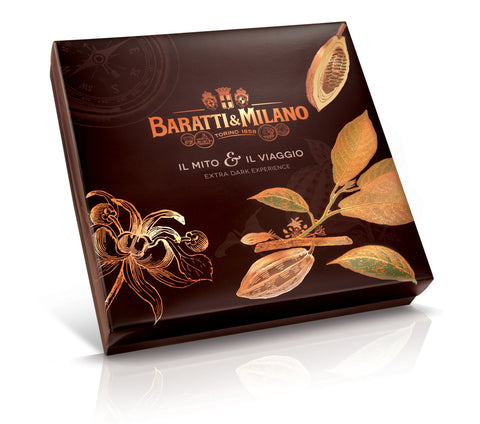 Baratti & Milano Extra Dark Experience Prestige Box is a deep luscious color brown with gold images of the Baratti & Milano logo and whimsical imagery of gold Cacao plants and beans. Also shows an image of a sketch of a compass on the box. All on a white background.