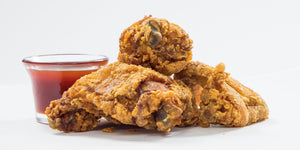 crispy golden fried chicken with a side of kents honey and hot sauce