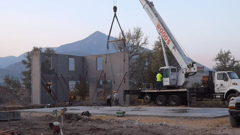 crane installing tilt-up concrete walls for modern utah home