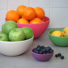 four nesting bowls in bright colors with fruit