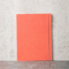 coral notebook with let's meet on the cover