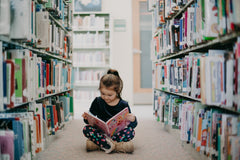 little girl sitting in the library aisle reading