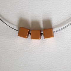 modern necklace with three bronze squares on a silver chain