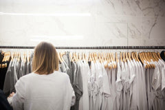 woman browsing neutral color t shirts on a rack at a pop up shop