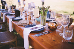 wooden table outside set for dinner party