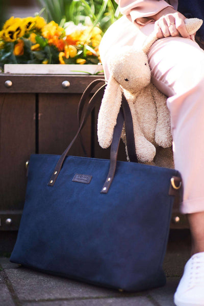Navy Wax and Dark Brown Diaper bag by O My Bag on the ground outside next to parent with stuffed animal.