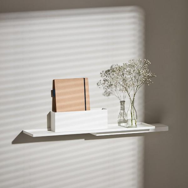 White Duplex Shelf by Puik hanging on a while with a plant and journal.
