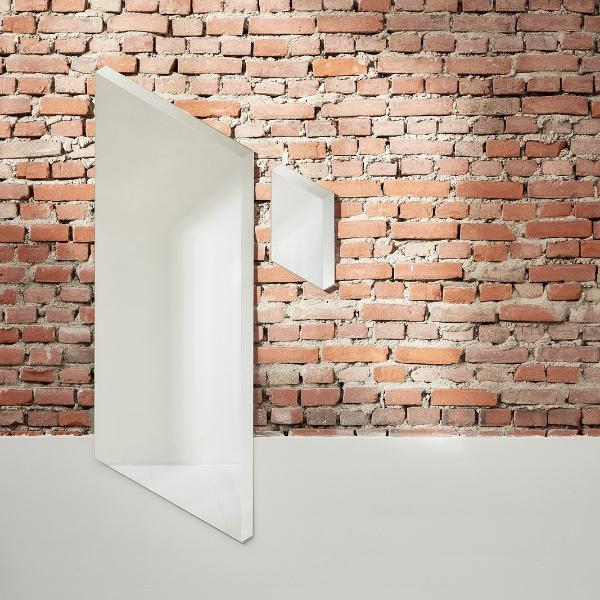 The Facett Mirror by Puik in small and medium against a brick wall.